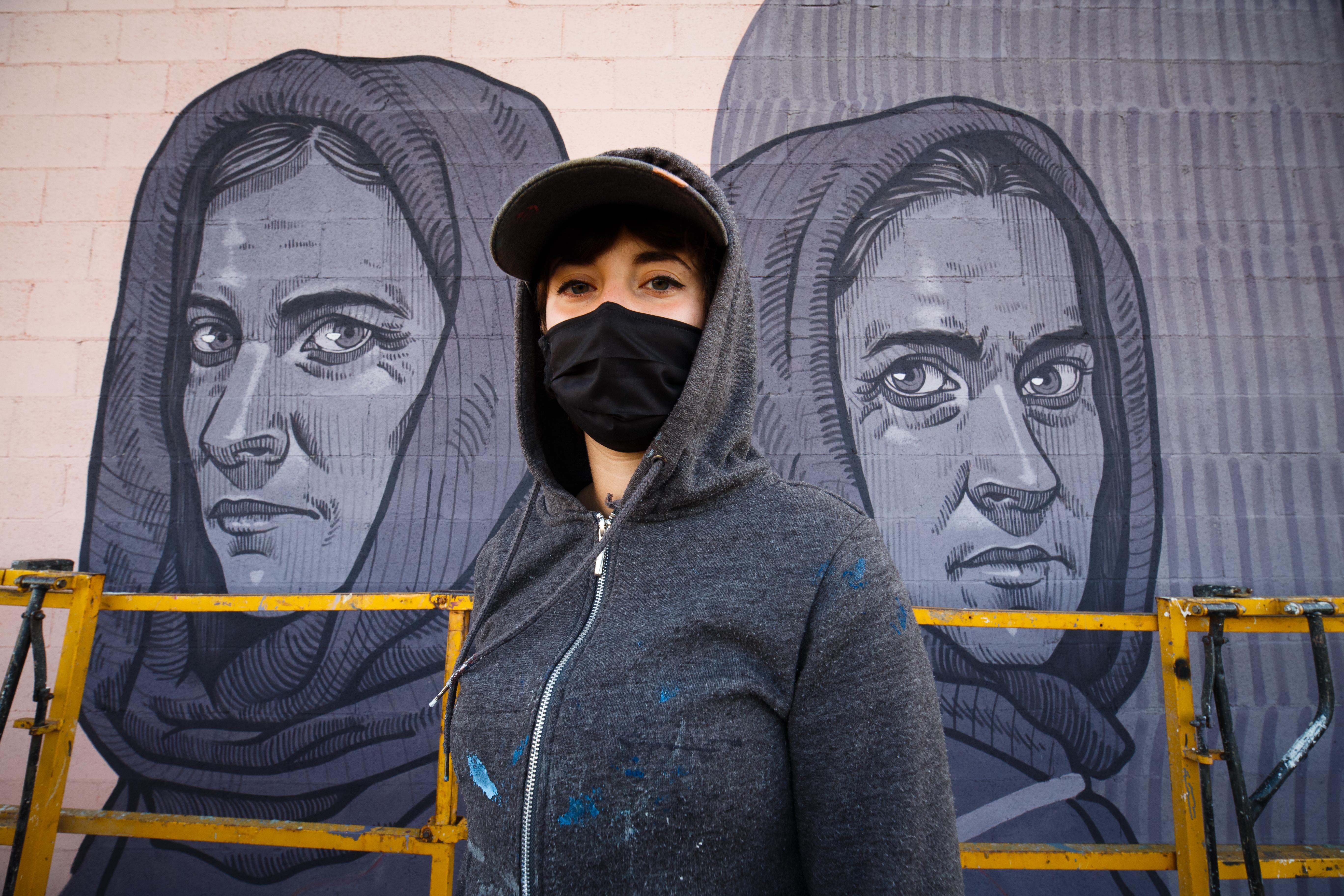 A artista Lidia Cao diante das figuras inspiradas en Aurora e Manuela Liste Forján no seu mural para o Delas Fest 2020