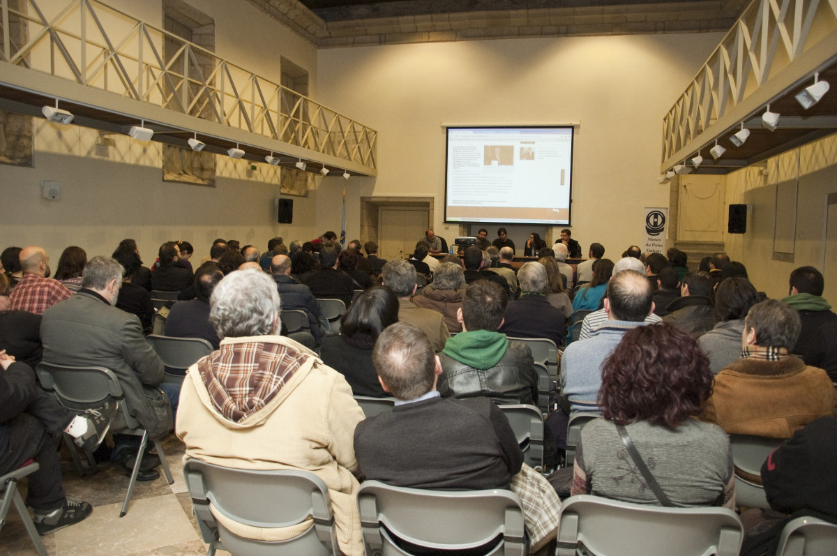 O público asistente ao acto observa a web