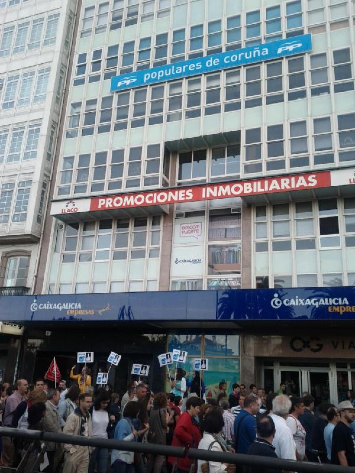 Unha manifestación pasa ante a sede do PP coruñés