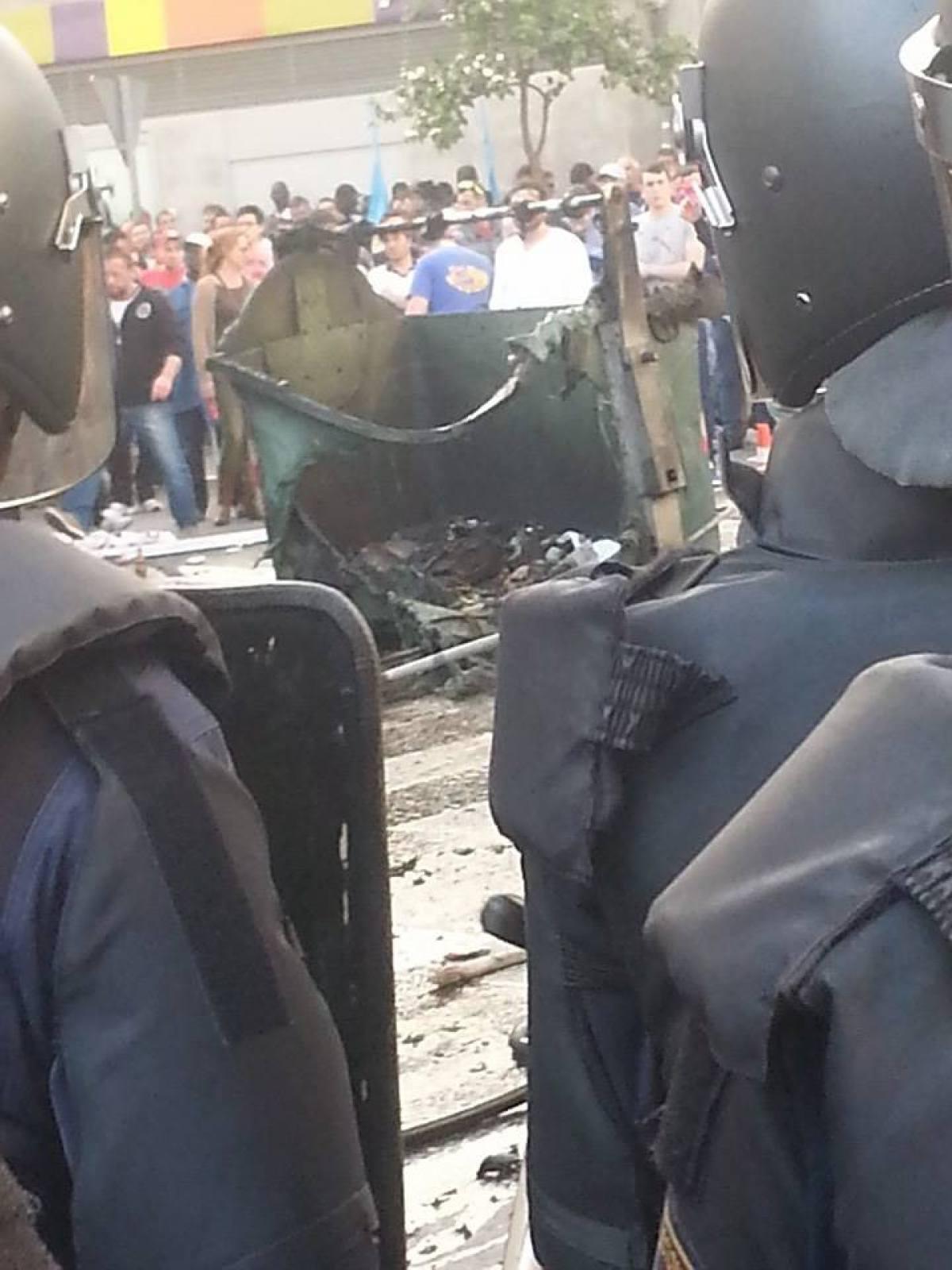 Policías ante un colector queimado